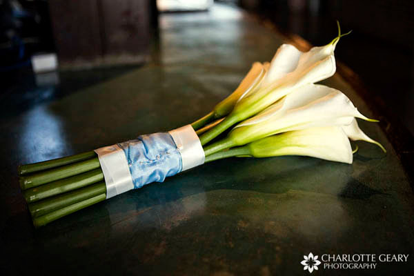 Bridal bouquet of white calla lilies, fastened with a light blue ribbon.