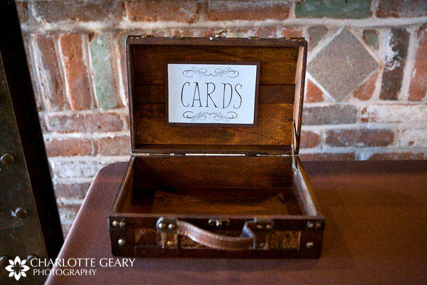 Antique suitcase used as a card box with a handmade blue and brown sign.