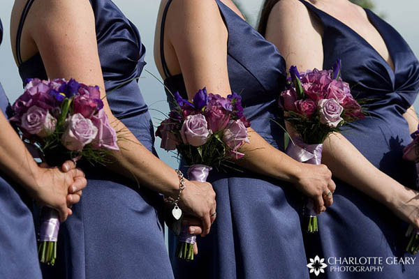 Bridesmaids with indigo blue dresses and blue and purple bouquets