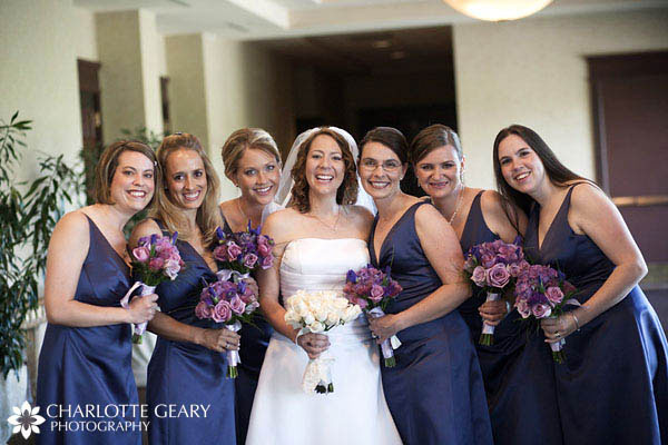 Bridesmaids in navy blue dresses with purple and blue bouquets