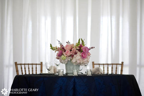 Wedding sweetheart table with navy blue linens and a pink centerpiece