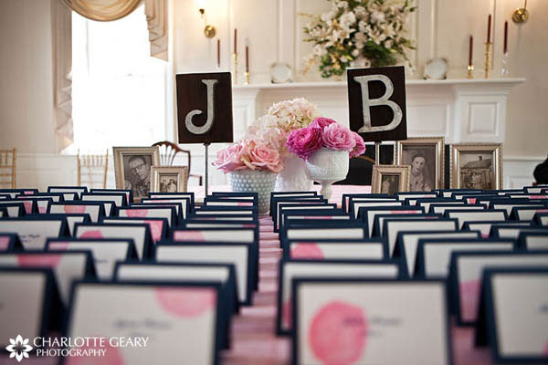 Blue and pink wedding place cards displayed with family photographs and the bride and groom\