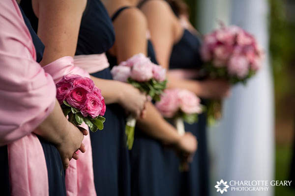 Bridesmaids in navy blue dresses and pink shawls with pink bouquets