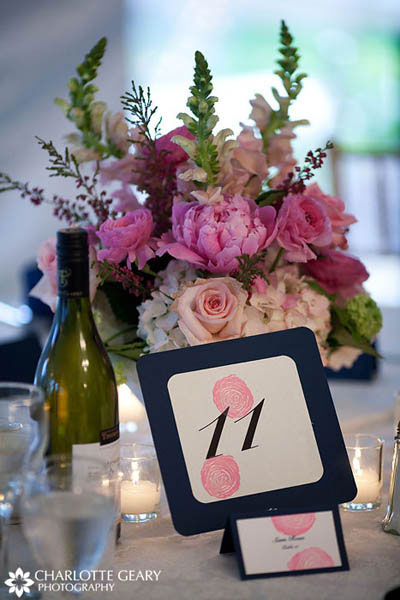 Wedding reception table number in blue and pink, with a centerpiece of pink flowers