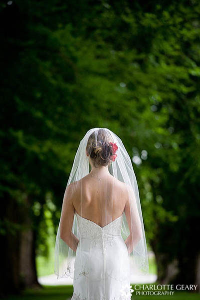 Bride in a scalloped fingertip-length veil, with a red flower in her hair