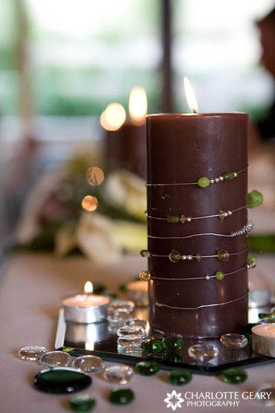 Brown candles decorated with green beads and stones