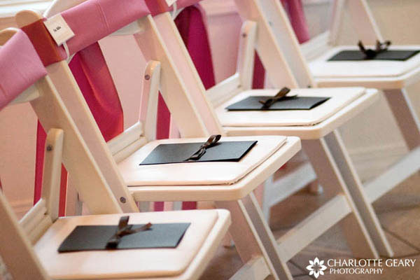 Brown wedding programs on chairs decorated in pink
