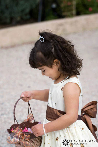 Flower girl in brown and white dress with a brown basket