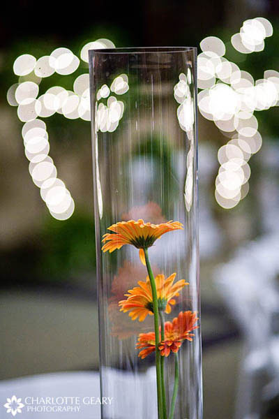 Wedding centerpiece with orange gerbera daisies in a tall vase