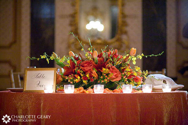 Wedding sweetheart table with orange, red, and  yellow centerpiece