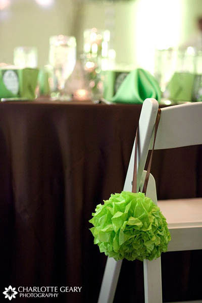 Green paper tissue ball decorating a brown wedding reception table