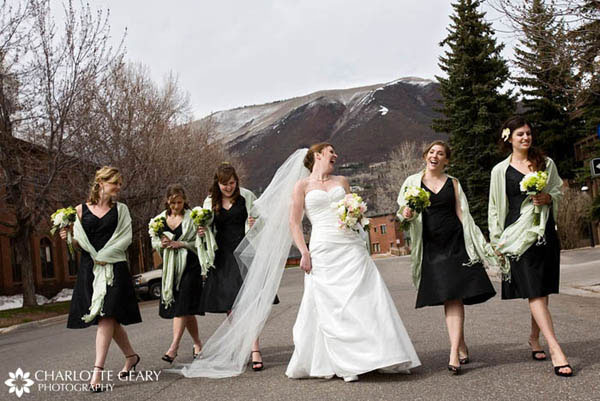 Bridesmaids in black dresses with light green shawls and bouquets