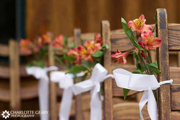 Orange flowers tied to the ends of each aisle