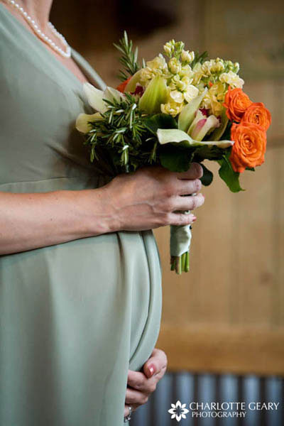Bridesmaid in light green dress with orange and green flowers