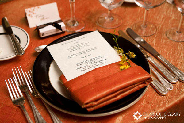 Autumn wedding place setting with orange linens, yellow flowers, and a menu card