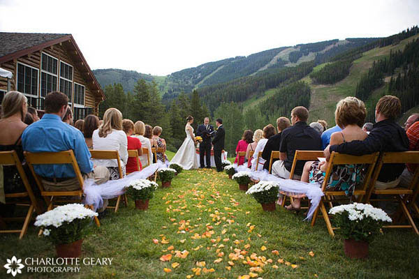 Yellow and orange rose petals along the wedding aisle