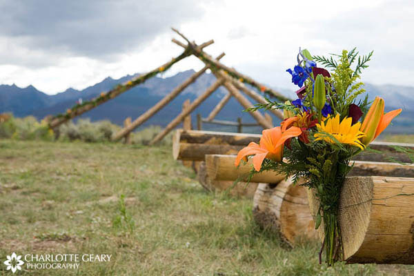 Arrangement of lilies and sunflowers at outdoor wedding ceremony