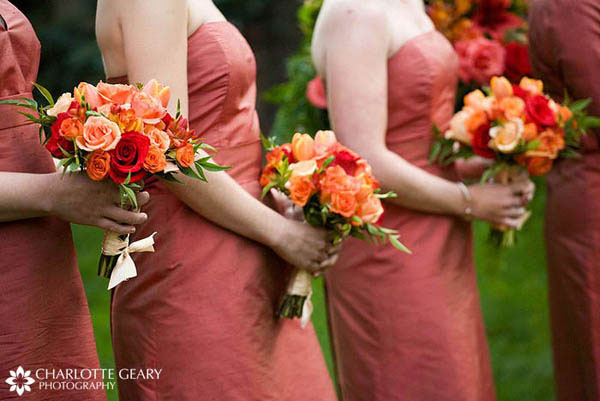 Bridesmaids in orange dresses with red and orange bouquets