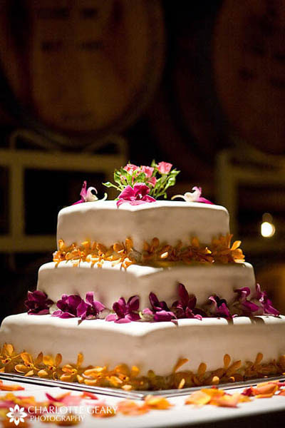 Square wedding cake with pink and orange orchids