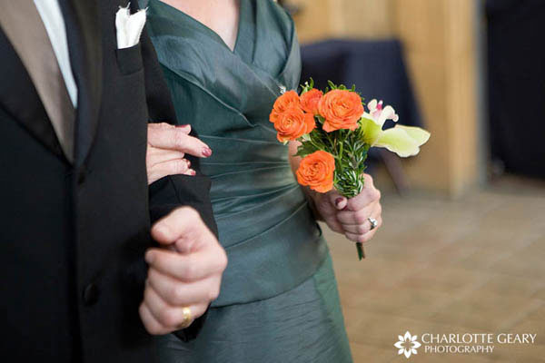 Mother of the bride in green dress with orange flowers