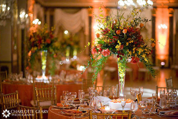 Autumn wedding centerpieces with orange, yellow, and red flowers