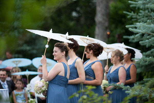 Bridesmaids with parasols during a rainy springtime wedding