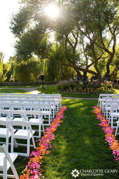 Pink and orange flower petals along the ceremony aisle