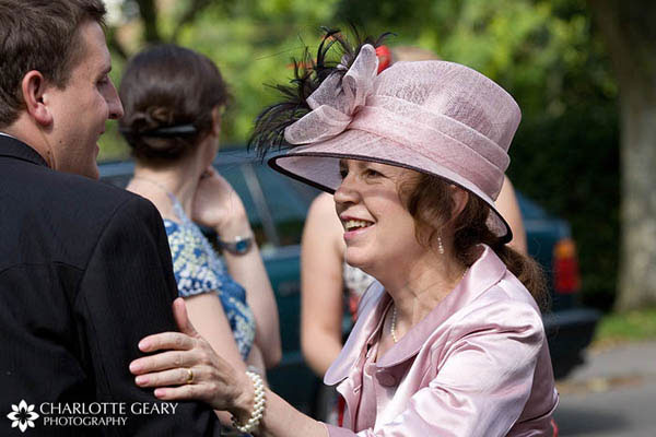 Mother of the groom in pink dress and hat