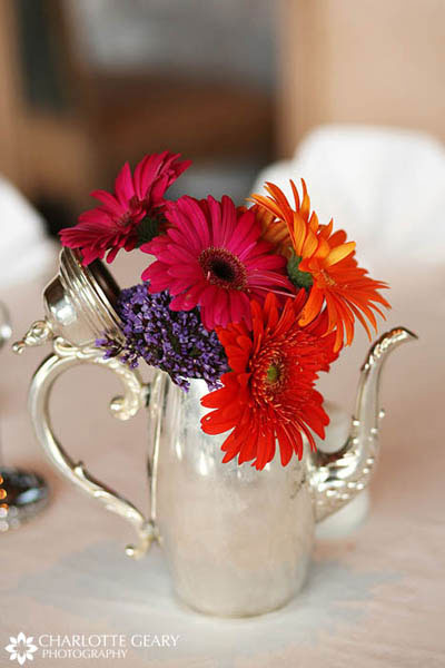 Colorful gerbera daisies in a silver teapot