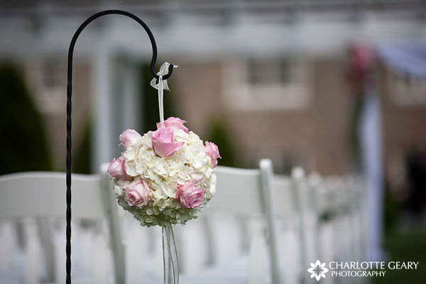 Pink and white flowers hung from shepherds hooks