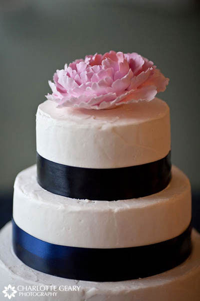 Wedding cake with navy blue ribbon and a pink sugar flower
