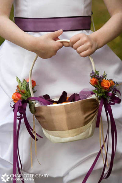 Flower girl with purple sash and purple and orange basket of flower petals