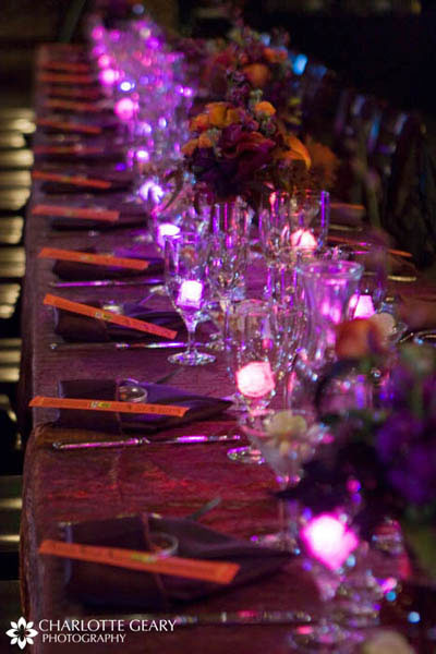 Table settings in orange and purple, with glowing purple ice cubes
