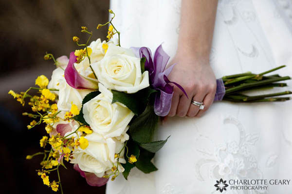 Bouquet of yellow and pink flowers with purple ribbon