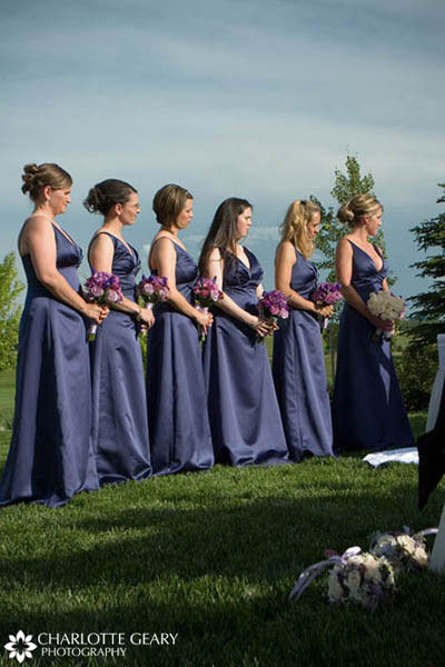 Bridesmaids in indigo blue dresses with purple and blue bouquets