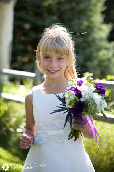 Flower girl with white dress and purple flowers
