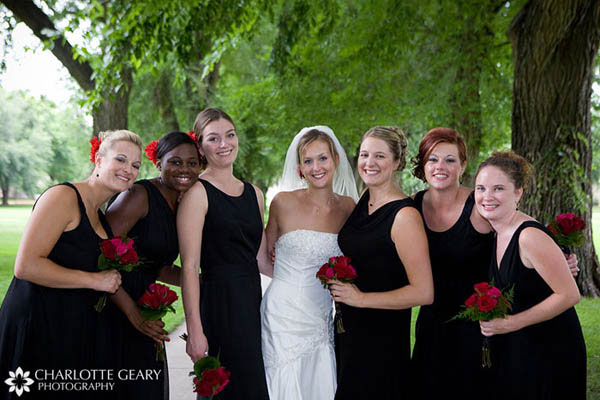 Bridesmaids in black dresses with red flowers