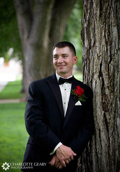 Groom in tuxedo with red boutonniere