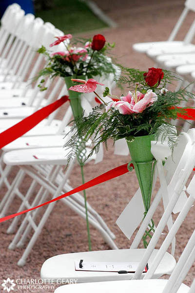 Red and green floral arrangements along the ceremony aisle