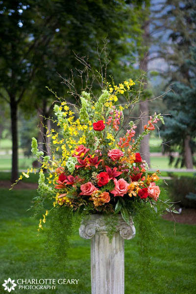 Ceremony floral arrangement in red, orange, pink, and yellow