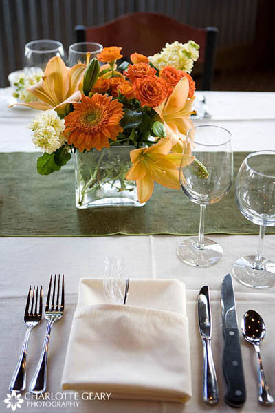 Reception table set with a green table runner and orange flowers