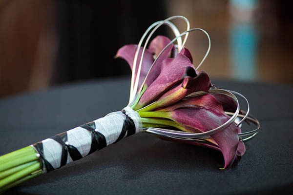 Bouquet of deep purple calla lilies tied with silver and black ribbons