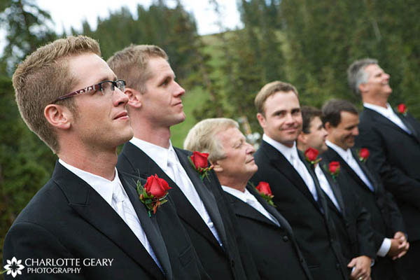 Groom and groomsmen in black suits with red rose boutonnieres