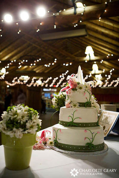 Green and white wedding cake decorated with wildflowers