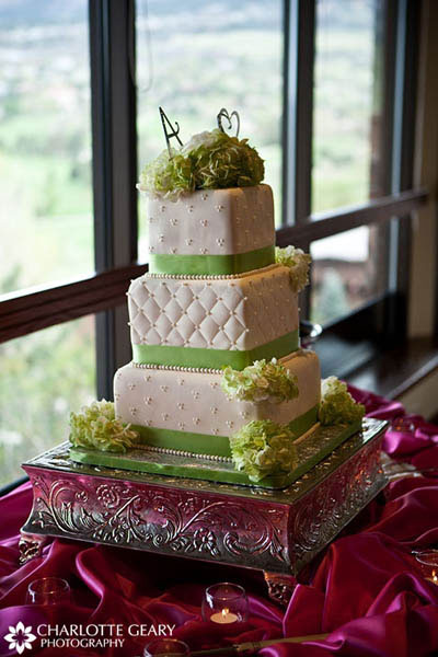 Square wedding cake with green trim and a silver cake platter