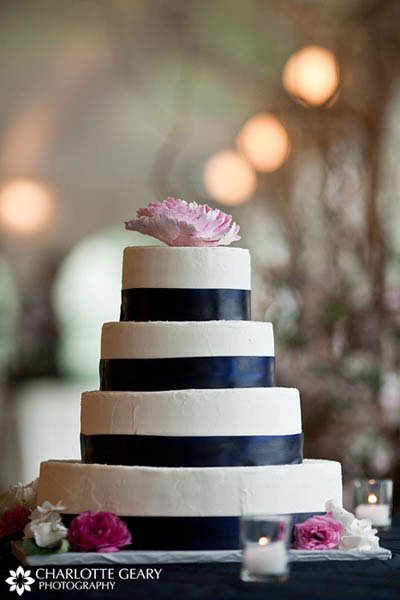 Wedding cake with navy blue ribbons and pink flowers