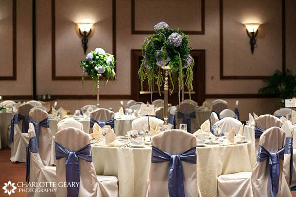 Ballroom decorated with blue and white chair covers and blue and green tall centerpieces