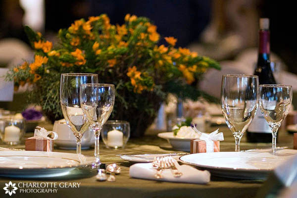 Wedding table settings with yellow centerpiece and gold favor boxes