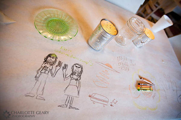 Wedding table covered in paper with crayons for guests to draw