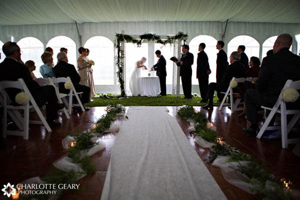 Wedding tent decorated with greenery and an aisle runner for the ceremony
